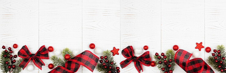 Fototapeta na wymiar Christmas border banner of ornaments, branches and red and black checked buffalo plaid ribbon. Top view on a white wood background.