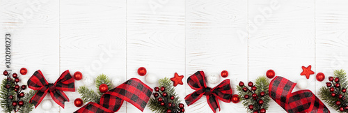 Christmas border banner of ornaments, branches and red and black checked buffalo plaid ribbon. Top view on a white wood background. - 302098273