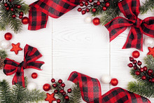 Christmas Frame Of Ornaments, Branches And Red And Black Checked Buffalo Plaid Ribbon. Top View On A White Wood Background.