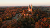 Fototapeta Na ścianę - Aerial view of a church on the top of hill and autumn forest, red foliage . Fall season, autumn colors. Countryside, Wisconsin. Drone shots at sunset