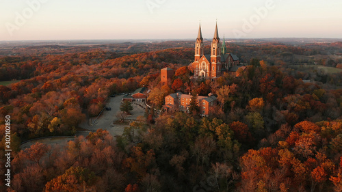 Fotografiet Aerial view of a church on the top of hill and autumn forest, red foliage