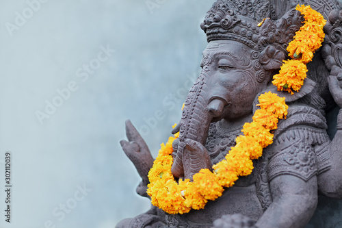 Ganesha sitting in meditating yoga pose in front of hindu temple Fototapeta