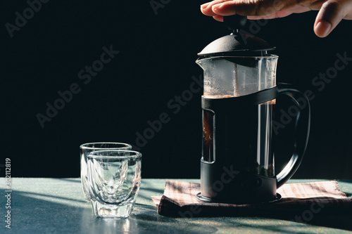 Wall Murals Cafe Aromatic coffees in French press coffee maker with couple glass and Antique coffee bean grinder using hand crank,Hot drink is good for health,Wood table,Black background,Natural light,Healthy Eating.