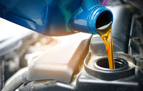 Fototapeta Refueling and pouring oil quality into the engine motor car Transmission and Maintenance Gear .Energy fuel concept. obraz