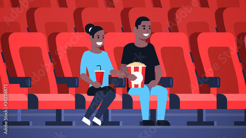couple watching movie sitting in cinema with popcorn and cola african american m Slika na platnu