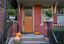Front Porch Of Older Brick House With Pumpkins And Flower Pots