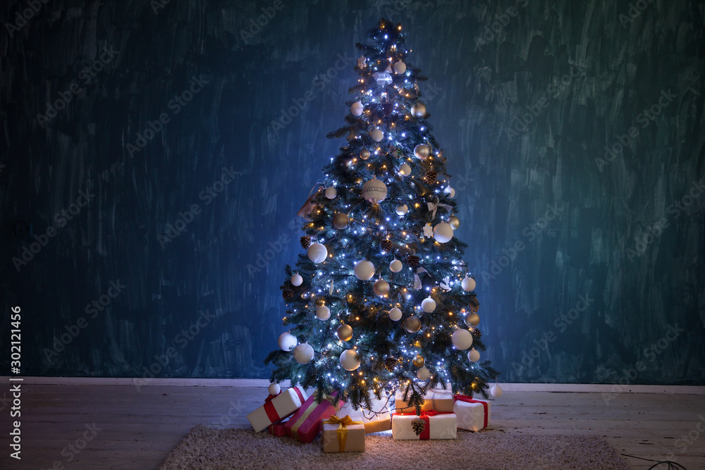 Fototapeta Christmas tree garland lights with gifts of new year holiday winter