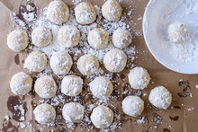 Finished Holiday Batch Of Russian Tea Cake Cookies Covered In Powered Sugar Cooling On Brown Paper, White Bowl
