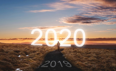 New year and new achievements concept. a man walking forward to 2020 leaving 2019 on the way behind