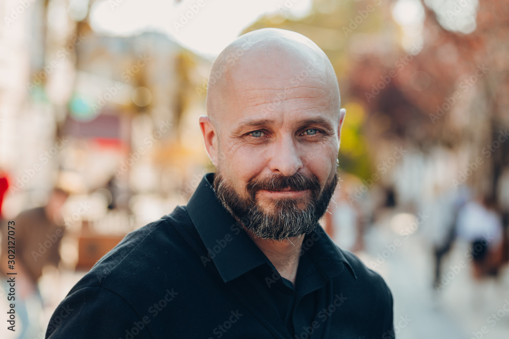 Fototapeta Outdoor portrait of a 50 year old happy man wearing a black shirt and glasses