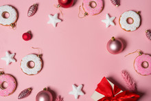 Paper Pink Background With Christmas Decoration Balls, Donuts, Gift And Stars.   Flat Lay, Top View. Christmas Card Conception.