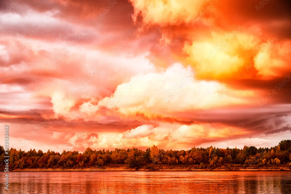 Fototapeta Sky with fantastic, amazing, stormy, disturbing red clouds over the river on a summer or autumn evening
