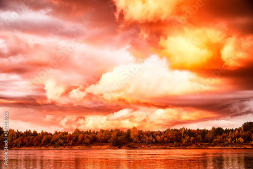 Leinwand Poster  Sky with fantastic, amazing, stormy, disturbing red clouds over the river on a s