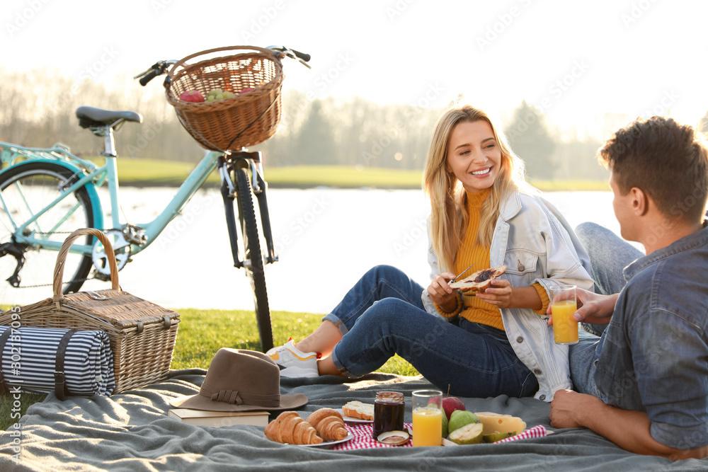 Fototapeta Happy young couple having picnic near lake on sunny day
