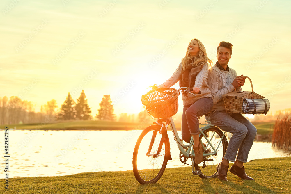 Fototapeta Young couple with bicycle and picnic basket near lake on sunny day