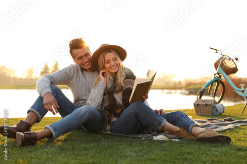 Cuadros en Lienzo  Happy young couple reading book while having picnic outdoors