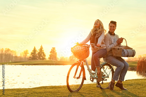 Obraz Young couple with bicycle and picnic basket near lake on sunny day - fototapety do salonu