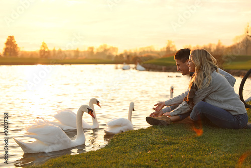 Fotobehang Zwaan Young couple near lake with swans at sunset. Perfect place for picnic