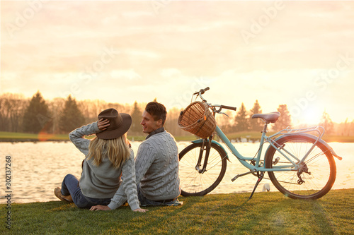 Obraz Young couple near lake at sunset. Perfect place for picnic - fototapety do salonu