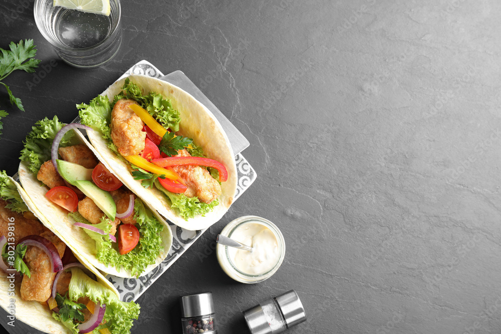 Fototapeta Delicious fish tacos served on grey table, flat lay with space for text