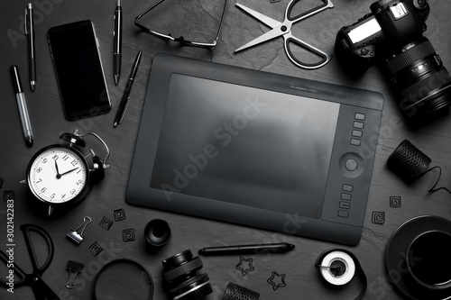Fotografía  Flat lay composition with graphic drawing tablet and different office items on black table