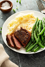 Traditional Dinner Meal With A Bacon Wrapped Steak, Green Beans And Mashed Potatoes