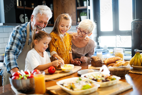 Fotografia Happy senior couple having breakfast with their grandchildren at home