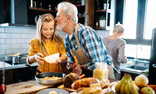 Happy young girl and her grandfather cooking together in kitchen Wallpaper Mural