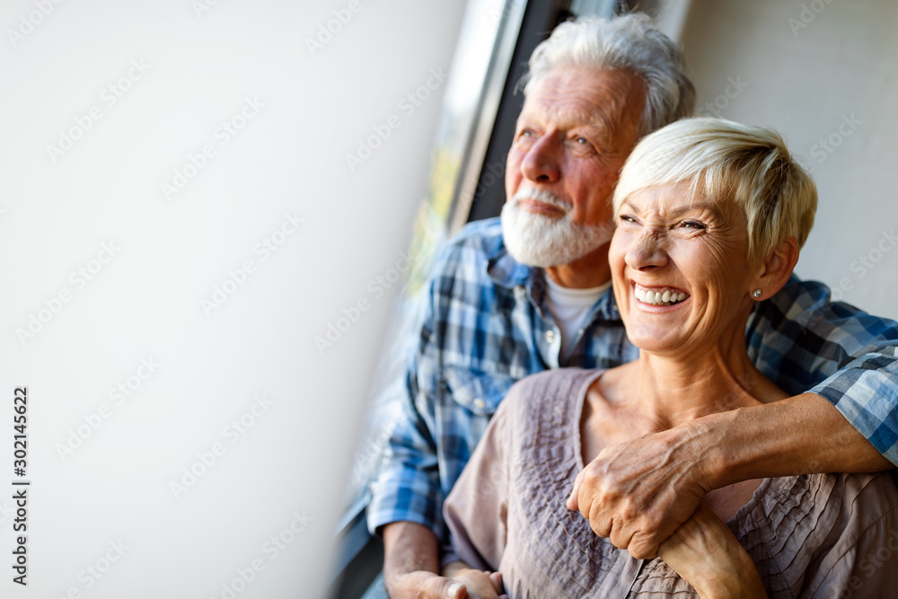 Fototapeta Happy senior couple in love hugging and bonding with true emotions at home