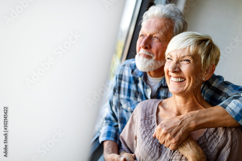 Obraz Happy senior couple in love hugging and bonding with true emotions at home - fototapety do salonu