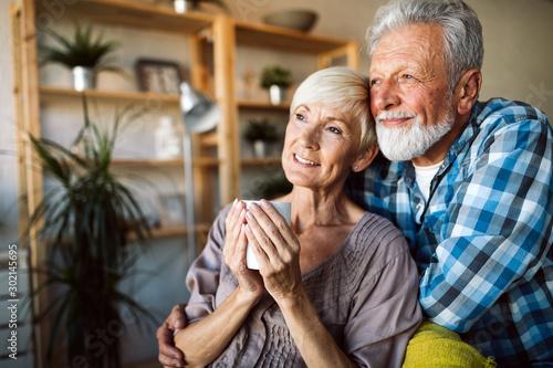 Fototapeta Happy romantic senior couple hugging and enjoying retirement at home obraz