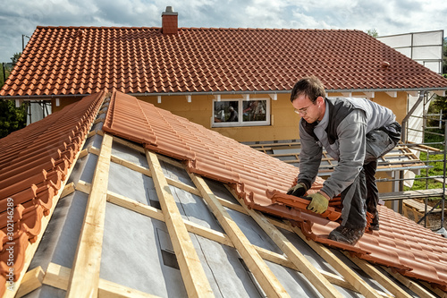 Photographie Roofer at work, installing clay roof tiles, Germany