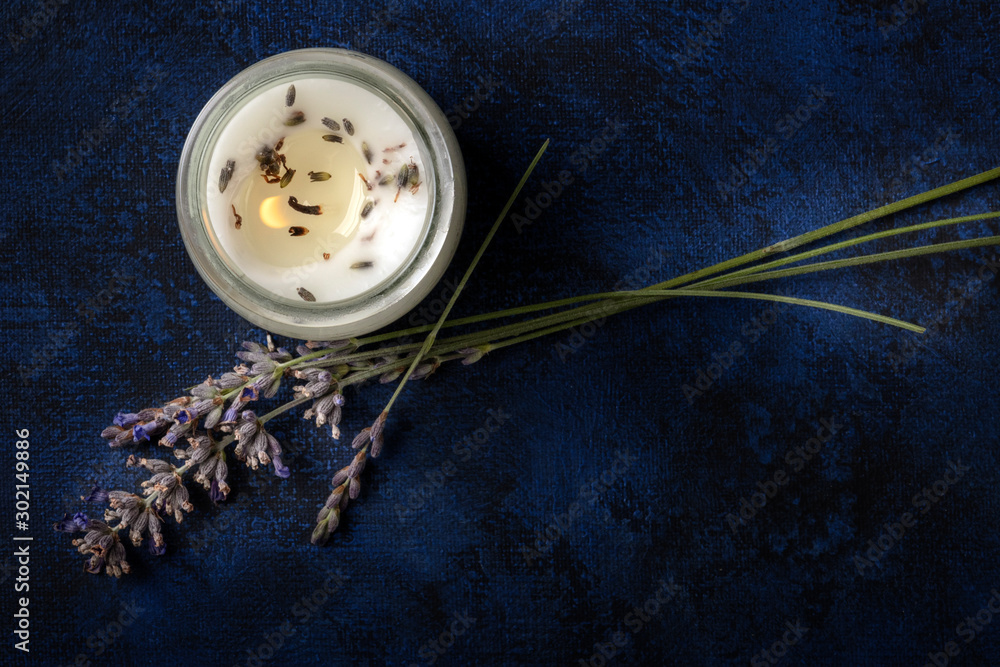 Fototapety, obrazy: A burning lavender scented candle, overhead shot on a dark background with a place for text. Zero waste Christmas concept, a handmade New Year gift in a recycled glass jar