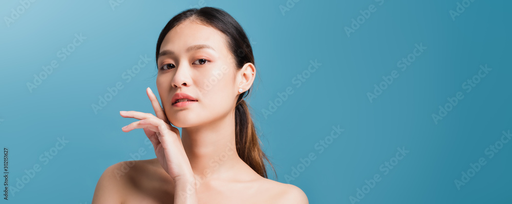 Fototapeta Portrait of confident beautiful asian woman with hand beside face and looking to camera isolated on blue color background with studio shot.Skincare for healthy face concept.