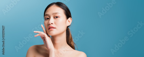 Fototapeta  Portrait of confident beautiful asian woman with hand beside face and looking to camera isolated on blue color background with studio shot