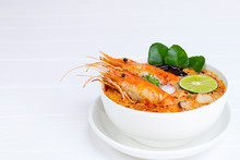 Tom Yum Goong Or Shrimp Soup Spicy Sour Soup Traditional Food In Thailand Contains Chili, Lime, Ginger, Galangal, Lemongrass, Lime Leaf, From Top View On A White Wood Background.