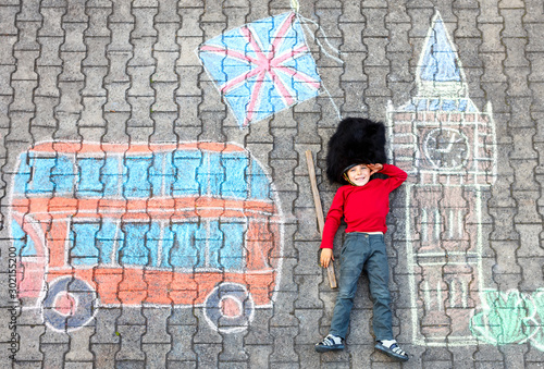 Photo Happy little kid boy in british queen's guard soldier uniform having fun with London picture drawing with colorful chalks