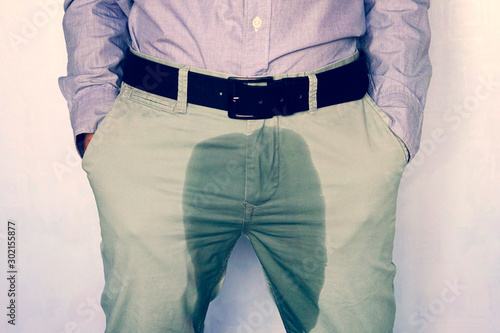 Fototapeta A man standing in wet pants against the wall