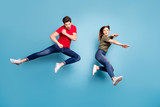 Full size photo of two people crazy funky successful married ninja couple jump practice martial fighting exercises wear green red t-shirt modern outfit isolated over blue color background