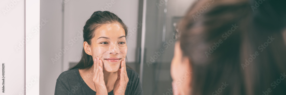 Fototapeta Face wash young Asian woman applying scrub exfoliating skin in beauty skincare routing morning lifestyle - Bathroom mirror panoramic banner panorama.