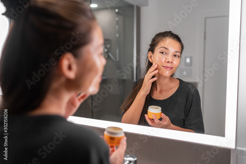 Fotografía  Skin care woman putting face mask product cleaning skincare beauty lifestyle - Asian woman looking in LED mirror in bathroom applying facial cleanser lotion