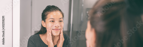 Fotomural  Face wash young Asian woman applying scrub exfoliating skin in beauty skincare routing morning lifestyle - Bathroom mirror panoramic banner panorama