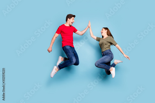 Great job. Full length profile side photo of cheerful two romantic people jump give highfive celebrate victory wear modern t-shirt denim jeans sneakers isolated blue color background