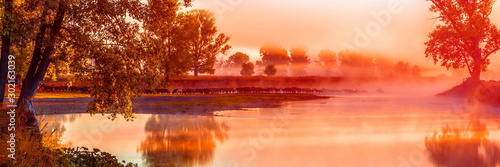 Spoed Foto op Canvas Koraal A large herd of horses crosses the river for a wade against the background of the morning mist at the first rays of the sun.
