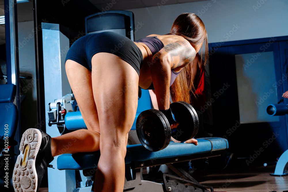 Fototapety, obrazy: Young woman bodybuilder doing dumbbell pulls in a gym