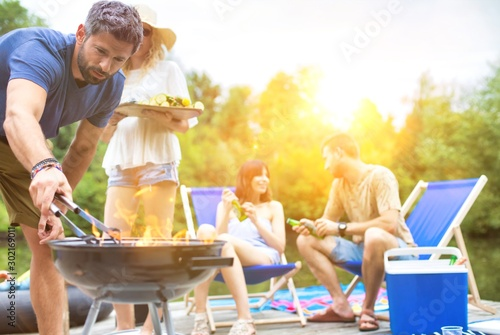 Foto  Man using bellows for preparing food in barbecue grill with friends on pier