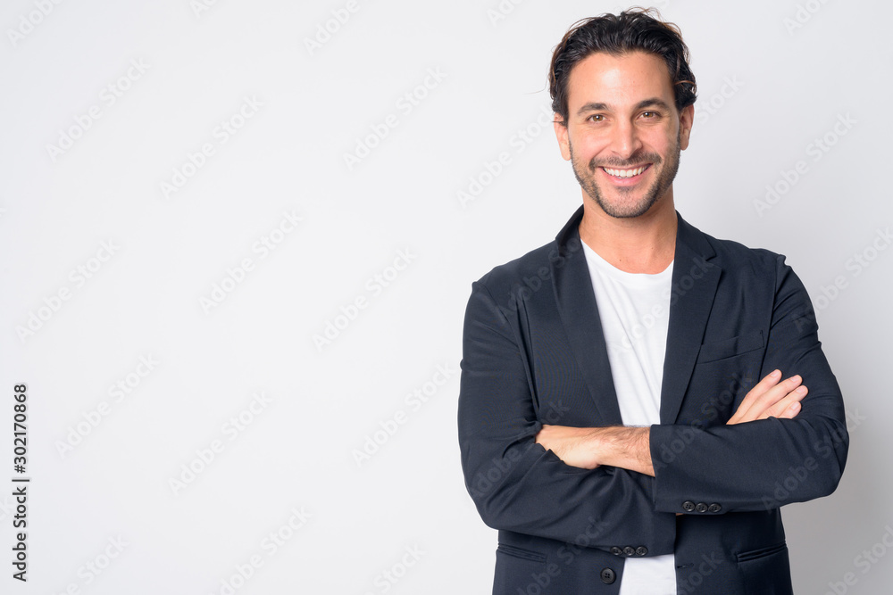 Fototapeta Portrait of happy handsome Hispanic businessman smiling with arms crossed
