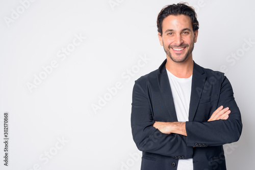 Obraz Portrait of happy handsome Hispanic businessman smiling with arms crossed - fototapety do salonu