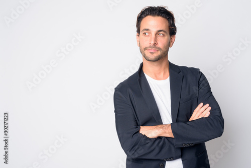 Fotografering Portrait of handsome Hispanic businessman thinking with arms crossed