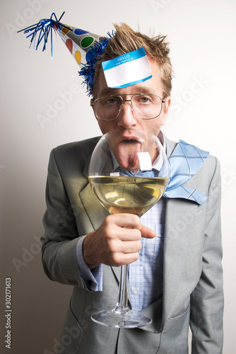 Fotografia, Obraz Drunken businessman wearing a party hat licking an oversized wine glass with a n